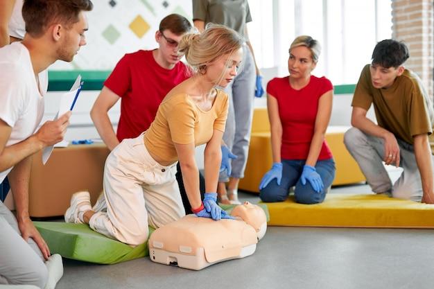 Blanke mensen oefenen een reanimatieoefening tijdens de les