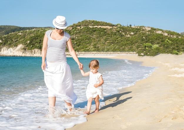 Blanke moeder die overdag met haar dochter op het strand loopt
