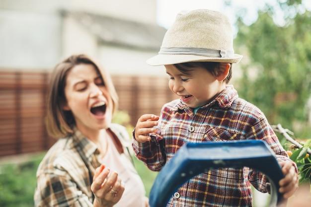 Blanke moeder met bruin haar en haar zoontje met een hoed die kersen eet en glimlacht