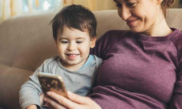 Blanke moeder met sproeten ontspannen op de bank met haar zoontje met behulp van een mobiel tijdens de quarantaine