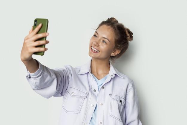 Blanke mooie meid lacht naar de telefoon terwijl ze een selfie maakt op een witte studiomuur