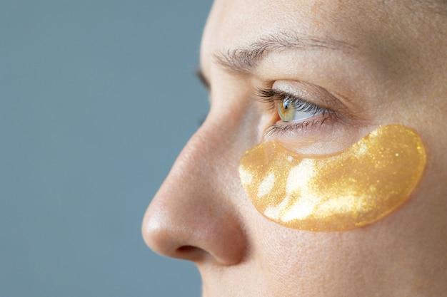 Blanke of europese vrouw met gouden vlekken onder haar ogen verzorgt haar huid hydraterend