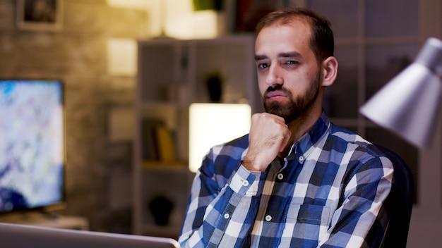 Blanke ondernemer denkt terwijl hij 's nachts op zijn laptop in zijn thuiskantoor werkt.