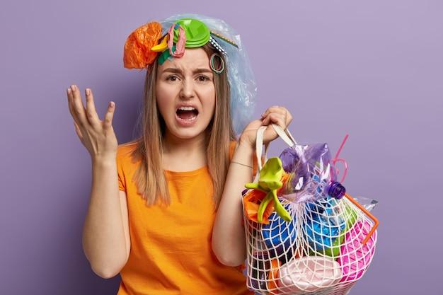 Blanke onrustige vrouw gebaart boos, probeert de planeet schoon te maken van plastic afval, schreeuwt wanhopig, houdt tas vol afval, draagt oranje t-shirt, staat tegen paarse muur.
