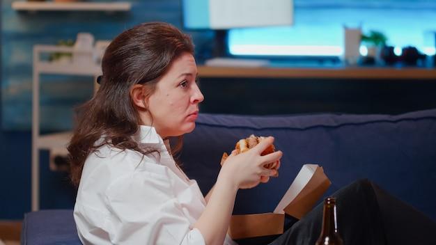 Blanke persoon geniet van vrije tijd met fastfood en televisie