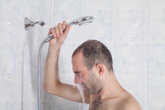 Blanke persoon in de badkamer. man die een douche neemt