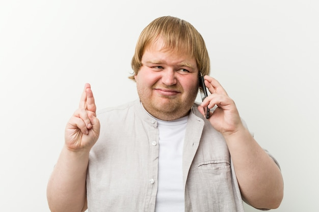 Blanke plus size man belt via telefoon kruising vingers voor geluk
