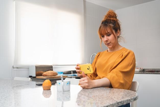 Blanke roodharige vrouw in een oranje shirt die een foto maakt van haar ontbijt en haar duim