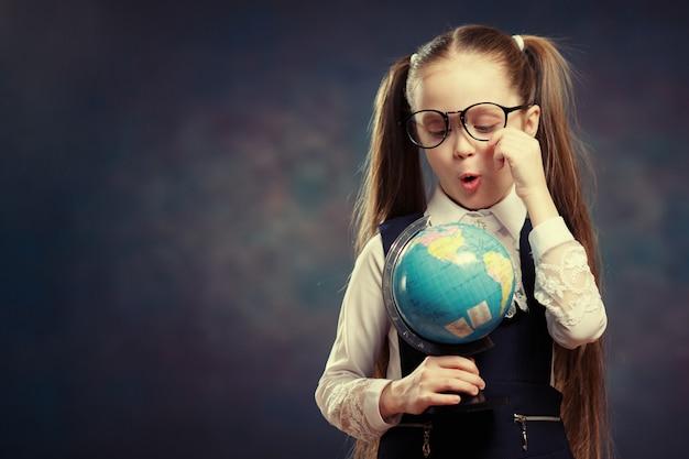 Blanke schoolmeisje bril dragen turn world globe.
