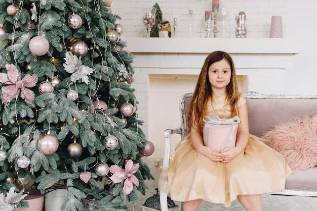 Blanke schoolmeisje zit in de buurt van versierde kerstboom met haar kerstcadeau