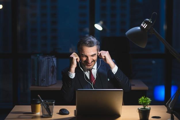 Blanke senior man aan het werk laat zitten op bureau in kantoor 's nachts. zakenman voelt zich gelukkig met conferentie op laptop en oortelefoons