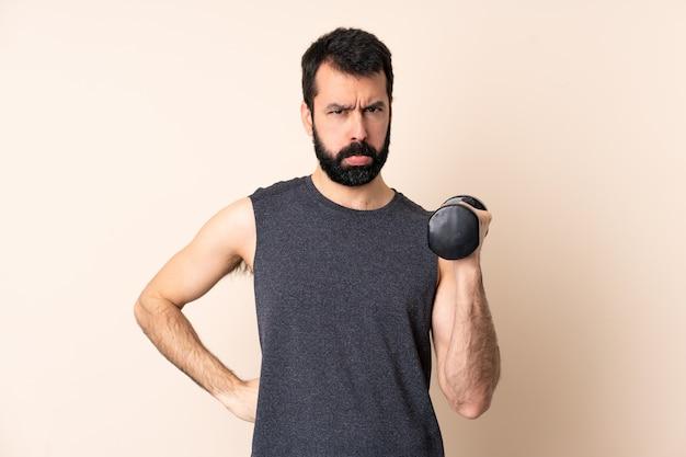 Blanke sport man met baard gewichtheffen over geïsoleerde boos maken