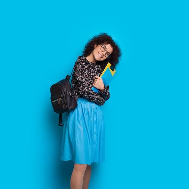 Blanke student met zwart krullend haar houdt enkele boeken vast terwijl hij zich voordeed op een blauwe muur