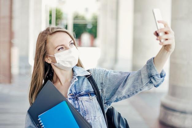 Blanke studente die een medisch masker draagt, houdt mappen en notitieboekjes in haar handen en belt via videoconferentie tijdens coronavirusquarantaine