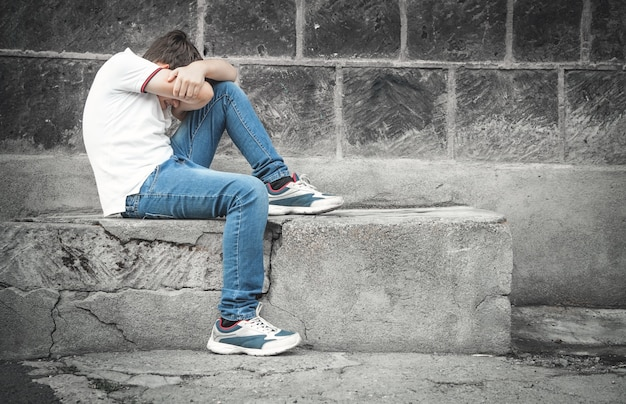 Blanke trieste jongen zittend in de straat.