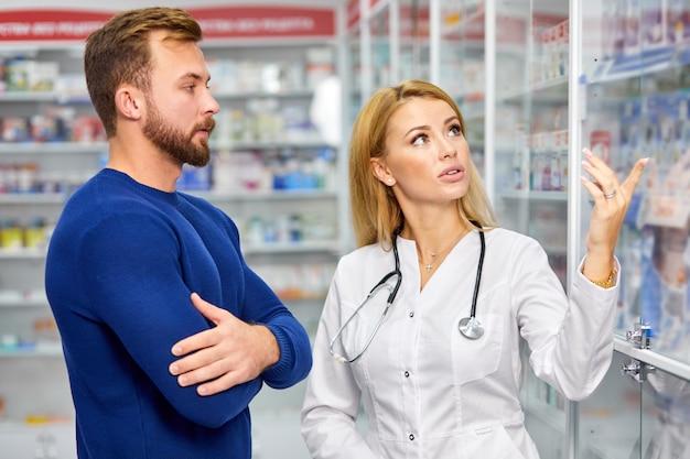 Blanke vriendelijke apotheker heeft een leuk gesprek met een cliënt