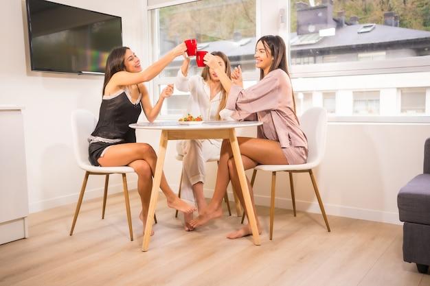Blanke vrienden op vakantie in een hotel aan het ontbijt, gekleed in nachtkleding en koffie drinken