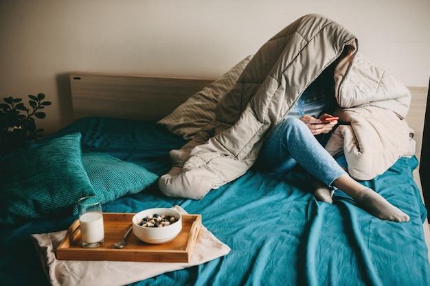 Blanke vrouw bedekt met een quilt is aan het chatten op de telefoon voordat ze melk met granen in bed eet