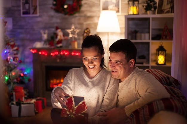 Blanke vrouw blij met haar eerste kerstdag van haar man. gloeiend cadeau.