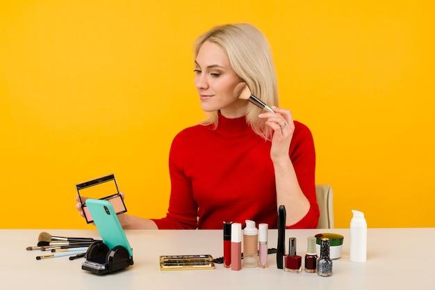 Blanke vrouw blogger die schoonheidsproducten presenteert en live uitzendt