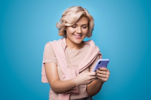 Blanke vrouw chatten op mobiel en lacht vrolijk op een blauwe studiomuur