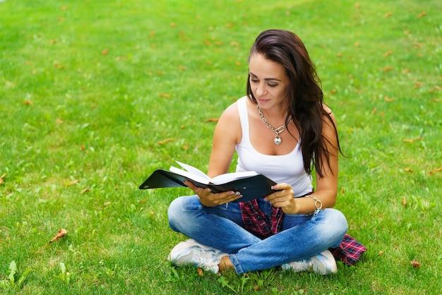 Blanke vrouw denkt en schrijft notities in notitieboekje, aantrekkelijk meisje dat haar werk plant, portret van vrouw zittend op groen grasveld, vrije tijd en ontspanning concept