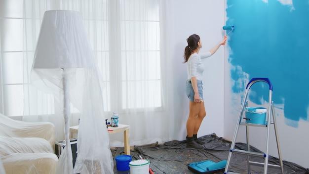 Blanke vrouw die appartement opknapt en muren schildert met rolborstel. appartement make-over. herinrichting en woningbouw tijdens renovatie en verbetering. reparatie en decoreren.