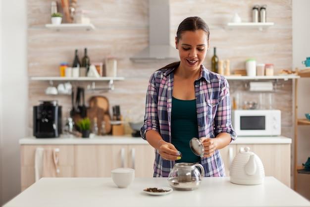 Blanke vrouw die aromatische kruiden gebruikt om 's ochtends hete thee te bereiden