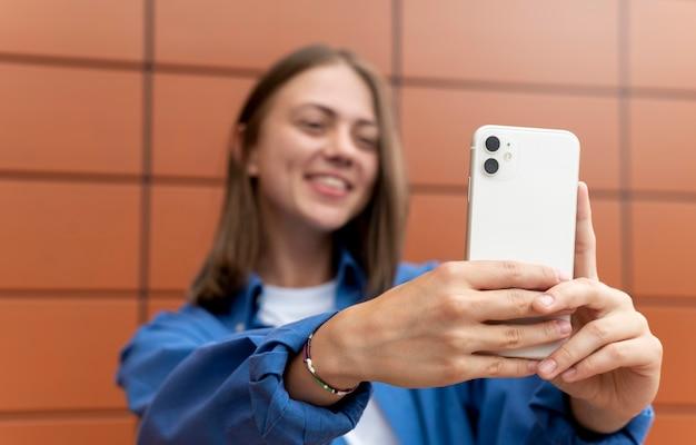 Blanke vrouw die buitenshuis een selfie maakt