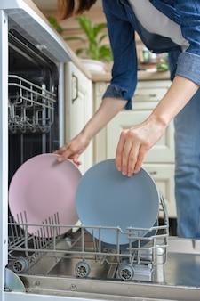 Blanke vrouw die de afwas met de hand afwast of ze in de vaatwasser laadt voor het wassen van huishoudelijk werk vrouwen
