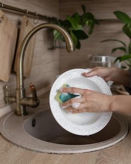 Blanke vrouw die de afwas met de hand afwast of ze in de vaatwasser laadt voor het wassen van huishoudelijk werk womens