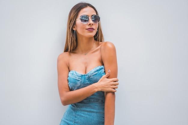 Blanke vrouw die een blauwe jurk en zonnebril draagt terwijl ze wegkijkt