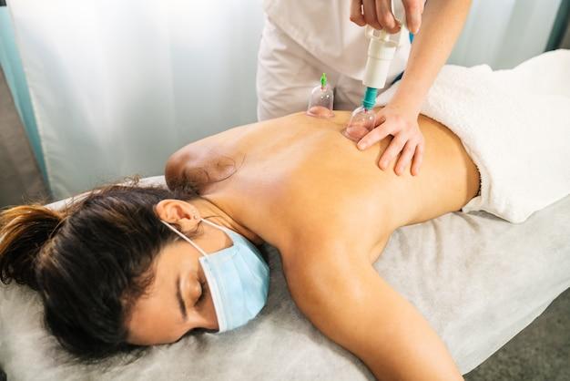 Blanke vrouw die een fysiotherapeutische vacuümmassage ontvangt met een vacuümbevelspuit om de rug van een cliënt te masseren terwijl ze op een brancard ligt met een gezichtsmasker vanwege het coronavirus covid 19