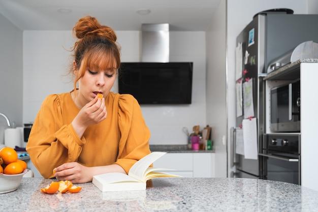 Blanke vrouw die een mandarijn eet terwijl ze thuis een boek leest op een tafel in de keuken