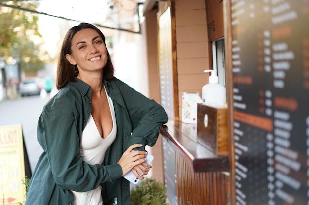 Blanke vrouw die koffie koopt bij een koffieplek, buiten raam zonsondergang tijd glimlachend