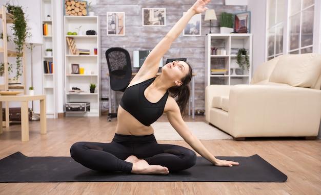 Blanke vrouw die op yoga lotus zit en haar rug uitstrekt in de woonkamer.