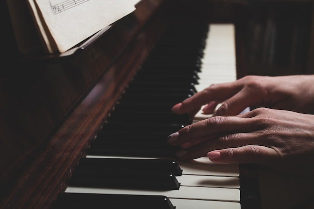Blanke vrouw die piano speelt in donkere close-up