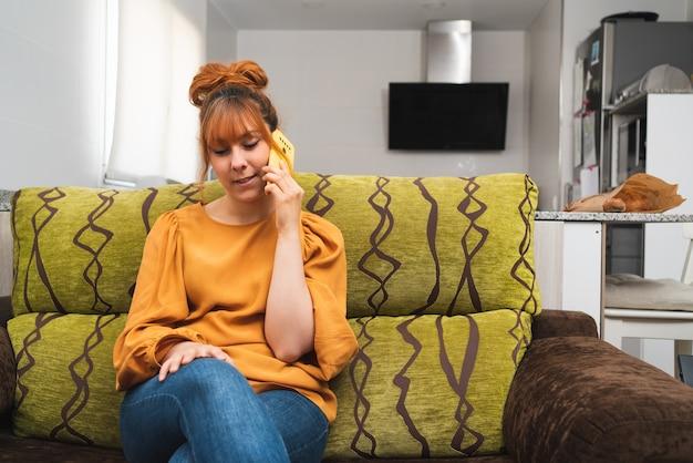 Blanke vrouw die thuis op de bank zit te praten aan haar telefoon met de keuken op de achtergrond