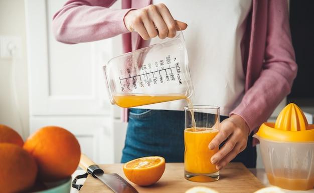 Blanke vrouw die wat vers sinaasappelsap in het glas zet na het met een pers in de keuken te hebben gemaakt