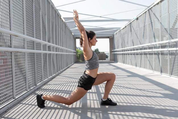 Blanke vrouw die zich uitstrekt voordat ze gaat sporten