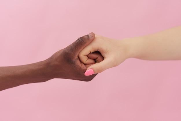 Blanke vrouw en afro-amerikaanse man hand in hand samen op roze achtergrond. racisme begrip.