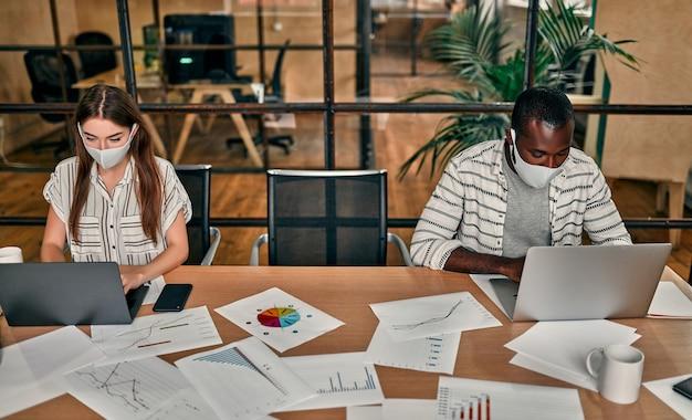 Blanke vrouw en afro-amerikaanse man met beschermende maskers, afstand houden, werken op laptops in een modern kantoor.
