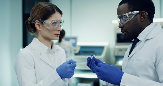 Blanke vrouw en afro-amerikaanse man, werknemers van het medisch laboratorium, doen een bloedonderzoek en bespreken het.