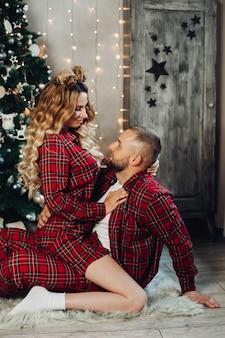Blanke vrouw en man ontspannen samen op de vloer in de woonkamer in kerstsfeer.