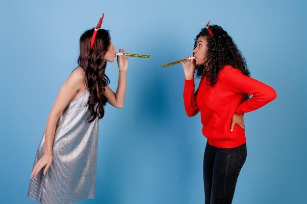 Blanke vrouw en zwarte meid waait kerst fluitjes