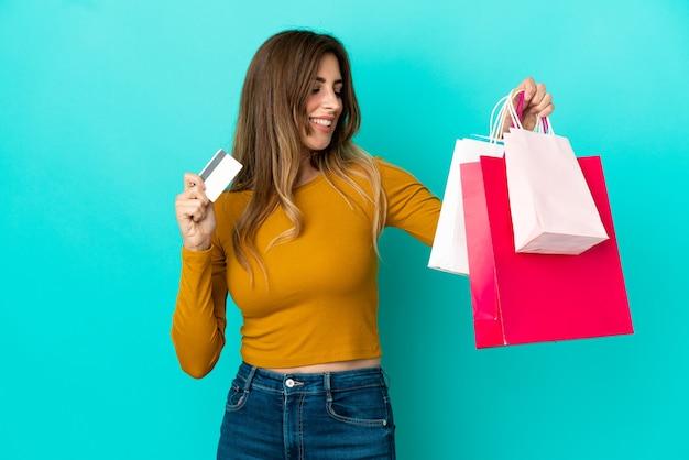 Blanke vrouw geïsoleerd op blauwe achtergrond met boodschappentassen en een creditcard