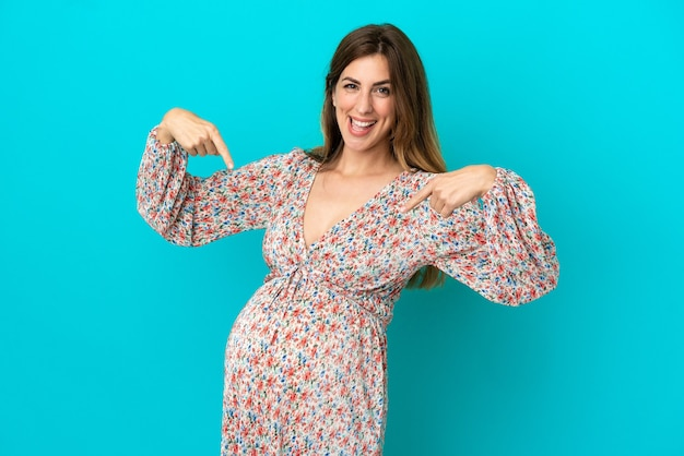 Blanke vrouw geïsoleerd op blauwe achtergrond zwanger en wijzend naar de buik