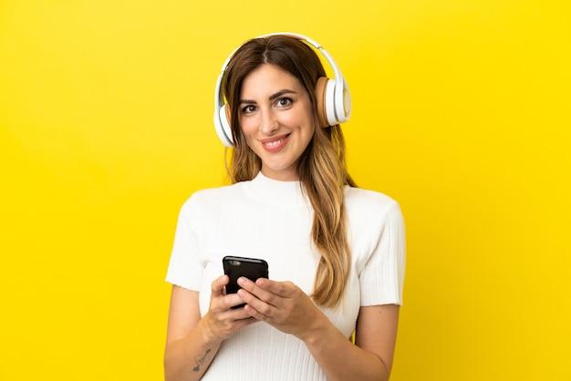 Blanke vrouw geïsoleerd op gele achtergrond die muziek luistert met een mobiel en naar voren kijkt