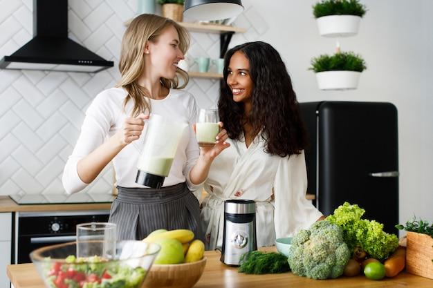 Blanke vrouw giet milkshake in een glas en afrikaanse vrouw kijkt naar haar