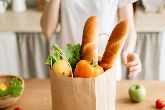 Blanke vrouw houdt eco boodschappentas met verse groenten en stokbrood in moderne keuken.